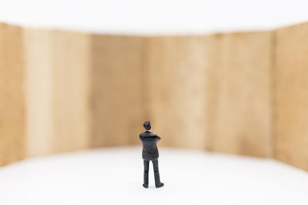 Miniatur des geschäftsmannes stehend und zur holzklotzspielzeugwand auf weißem hintergrund schauend