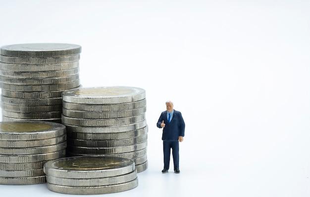 Miniatur des geschäftsmannmanagers stehend neben den münzen, die mit weißem hintergrund stapeln.