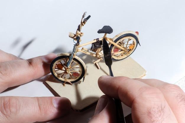Miniatur des hölzernen fahrrades auf weißem hintergrund. handcrafting prozess, hand des handwerkers, der das werkzeug hält.