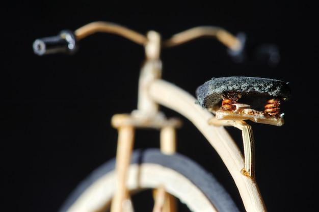 Miniatur des hölzernen hochradfahrrades auf schwarzem hintergrund. makro handcraft das detail, das vom fahrradsitz geschossen wird. old school fahrrad mit riesenrad.