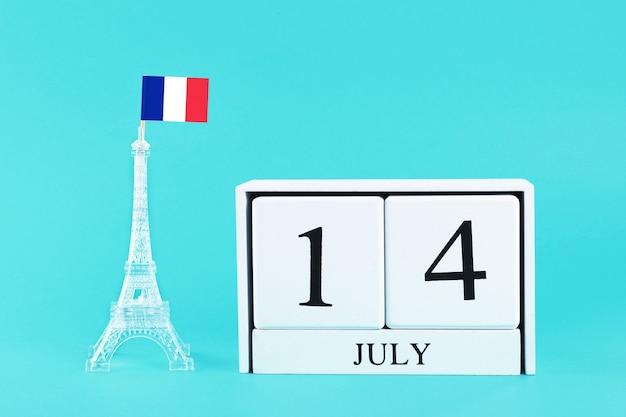 Miniatur-eiffelturm mit französischer flagge und kalender. das konzept ist der 14. juli, tag der