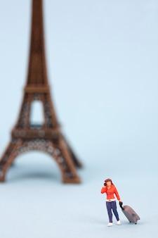 Miniatur-eiffelturm und frauentourist auf blauem hintergrund