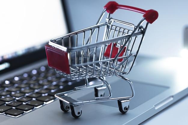 Miniatur-einkaufswagen auf der tastatur des laptops. konzept des online-shoppings und des e-commerce.