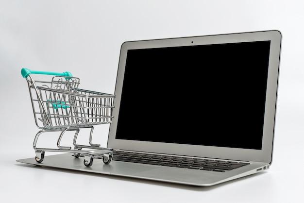 Miniatur-einkaufswagen auf laptop, lokalisiert auf heller oberfläche