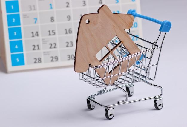 Miniatur-einkaufswagen, hausfigur mit desktop-kalender auf weißem hintergrund. weihnachtseinkäufe, schwarzer freitag, monatliches sonderangebotskonzept. hauskauf