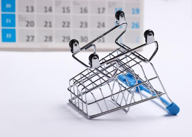 Miniatur-einkaufswagen mit desktop-kalender auf weißem hintergrund. weihnachtseinkäufe, schwarzer freitag, monatliches sonderangebotskonzept