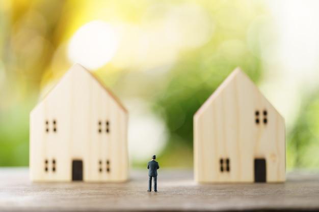Miniatur geschäftsleute stehen investment analysis housing oder investition