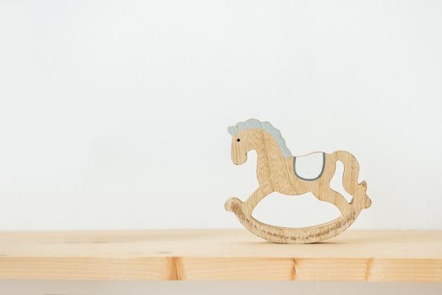 Miniatur hölzernes schaukelpferd für kleine puppe auf weißem hintergrund. kinderspielzeug