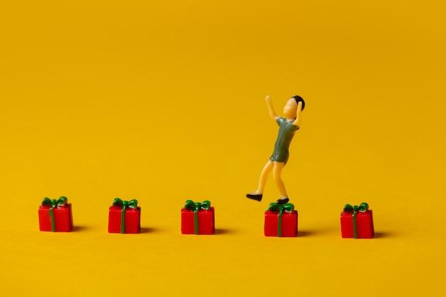 Miniatur-jungenfigur, die auf roten weihnachtsgeschenkboxen auf gelbem hintergrund springt