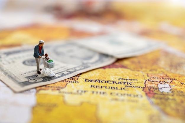 Miniatur-käufer mit einkaufswagen, der auf der geld- und weltkarte steht.