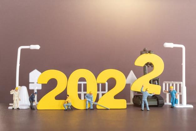 Miniatur-leute-arbeiter-team build-nummer 2022, frohes neues jahr-konzept