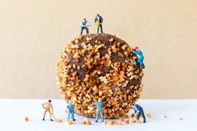 Miniatur-leute-arbeitsteam, das hausgemachte pralinen-butternut-donuts herstellt