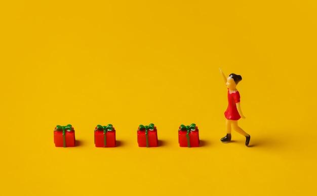 Miniatur-mädchenfigur neben roten weihnachtsgeschenkboxen auf gelbem hintergrund