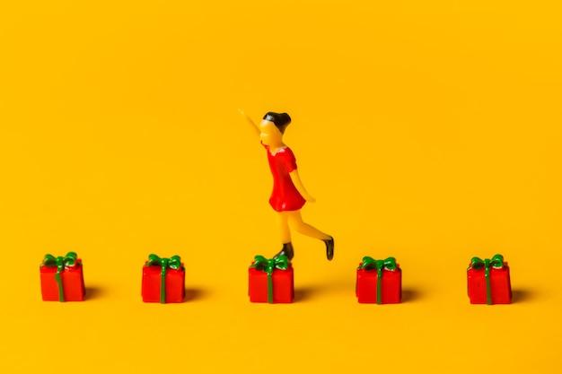 Miniatur-mädchenfigur springt auf rote weihnachtsgeschenkboxen auf gelbem hintergrund