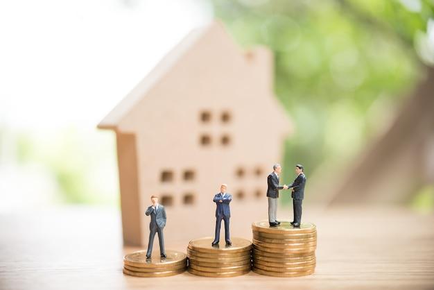 Miniatur menschen, immobilieninvestitionen. haus und münzen auf dem tisch.