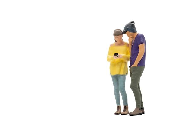 Miniatur-menschen, mann und frau in freizeitkleidung, die zusammen auf weißem hintergrund mit beschneidungspfad stehen