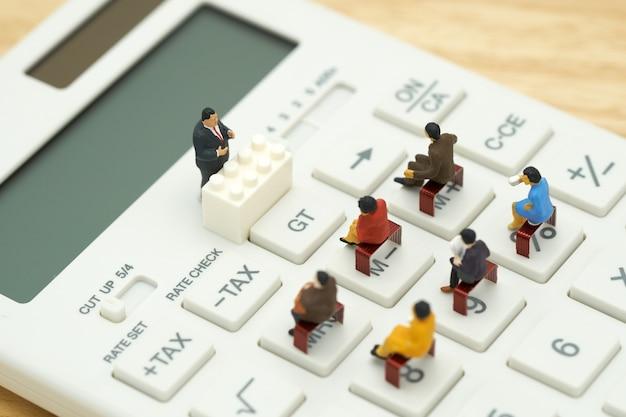 Miniatur-menschen pay-warteschlange jährliches einkommen (tax) für das jahr auf taschenrechner.