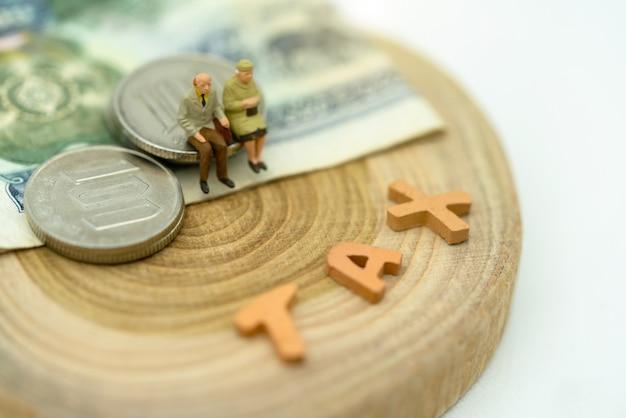 Miniatur von den alten leuten, die auf münzen sitzen, stapeln mit benennung