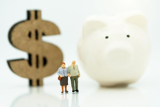 Miniatur von den alten leuten, die mit dollarzeichen und sparschwein stehen