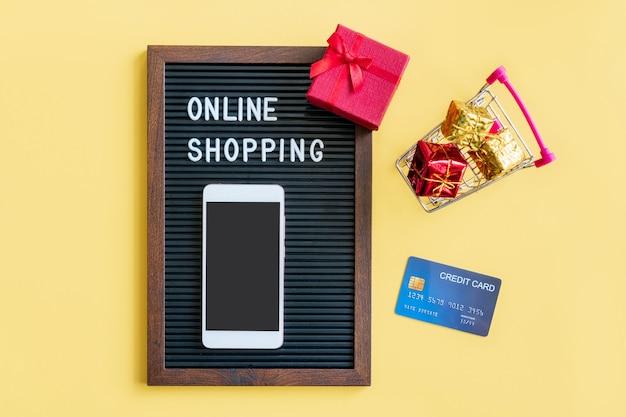 Miniatur von geschenkboxen in wagen, smartphone, wort auf schwarzem rahmen und kreditkarte auf gelb