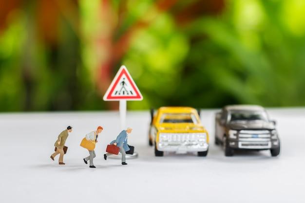 Miniatur von leuten, die die straße überqueren, gehen zum arbeitsbüro