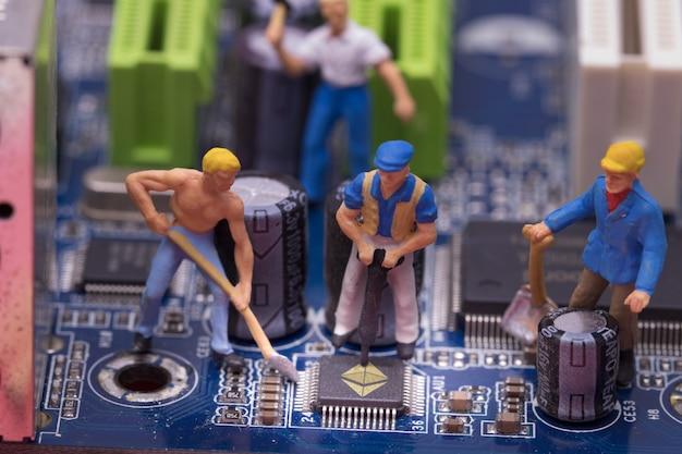 Miniaturarbeiter auf einem computer mainboard - atelieraufnahme