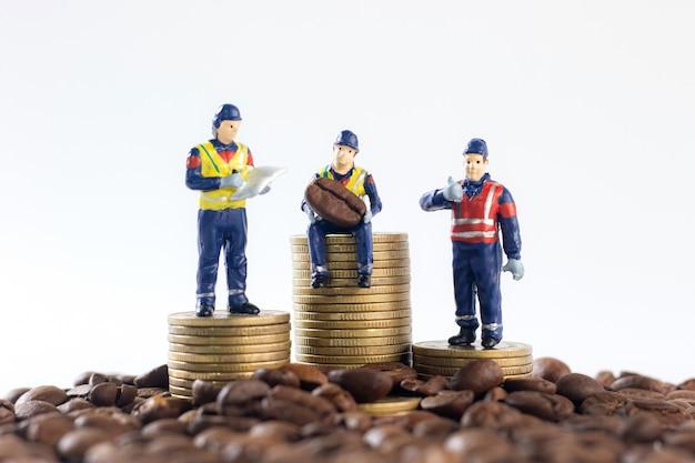 Miniaturarbeiter auf einem stapel von goldenen münzen, umgeben von kaffeebohnen