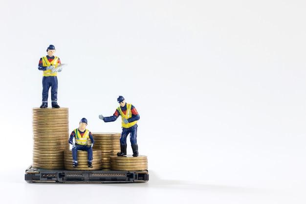 Miniaturarbeiter auf einem stapel von goldenen münzen