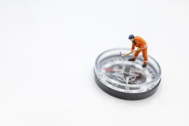 Miniaturarbeiter, der auf kompass gräbt. konzept, richtung und gelegenheit zu finden.