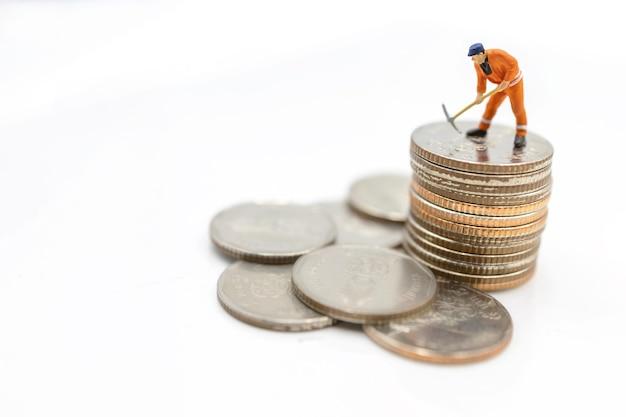 Miniaturarbeiter, der auf münzstapel gräbt. konzept von geld und investition.