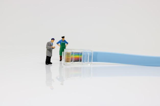 Miniaturarbeiter, der mit lan kabel steht.
