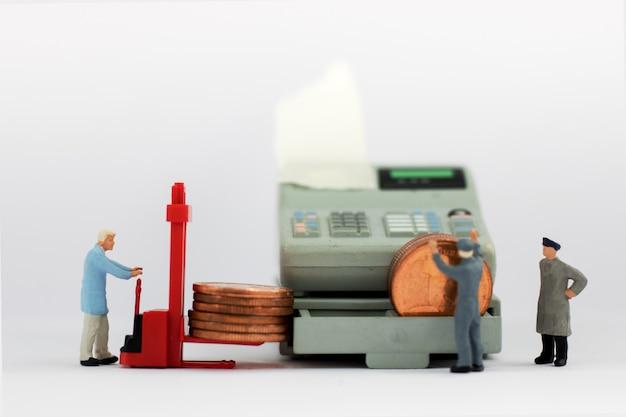 Miniaturarbeiter mit münzenstapel.