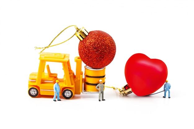 Miniaturarbeiter und kleiner gabelstapler mit herzball, valentinstag.