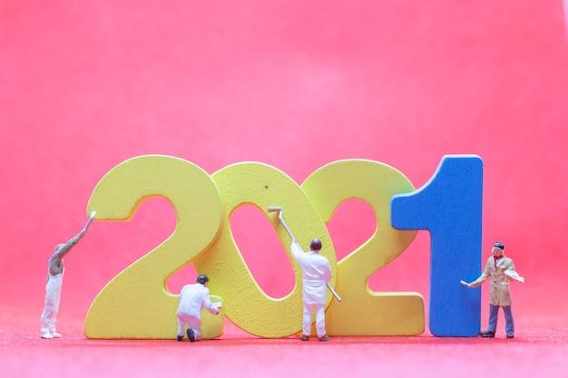 Miniaturarbeiterteam, das nummer 2021 malt, frohes neues jahr-konzept