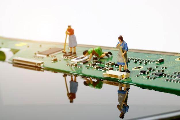 Miniaturarbeitskraft, die mainboard computer säubert.