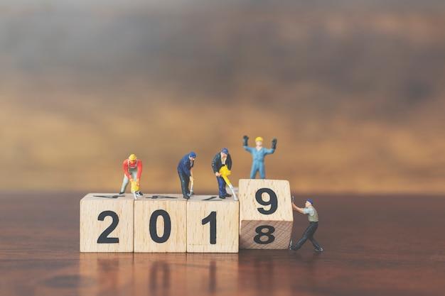 Miniaturarbeitskraftteam, das holzklotznummer 2019 errichtet
