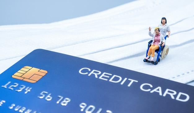 Miniaturarzt schickte alte frauen im rollstuhl nach hause während der krise covid-19, mit einer kreditkarte und einer maske auf grauem hintergrund.