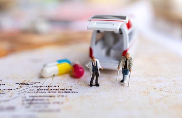 Miniaturarzt und patient stehend mit kapsel und krankenwagen. gesundheitswesen und medizinische konzepte.