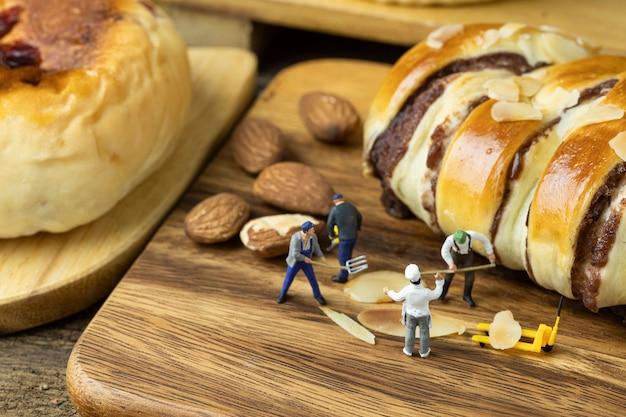 Miniaturbäcker, die brot auf holztablett backen.