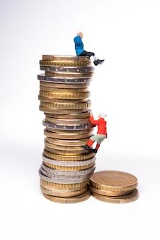 Miniaturbergsteiger, die auf dem stapel von münzen klettern