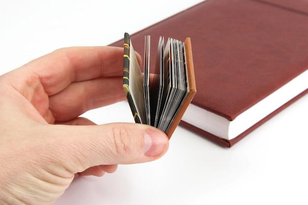 Miniaturbuch in der hand auf dem hintergrund der üblichen bücher