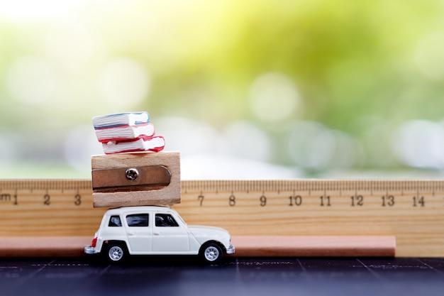 Miniaturen auto mit lineal, buch und bleistift. bildungs- oder geschäftskonzept.