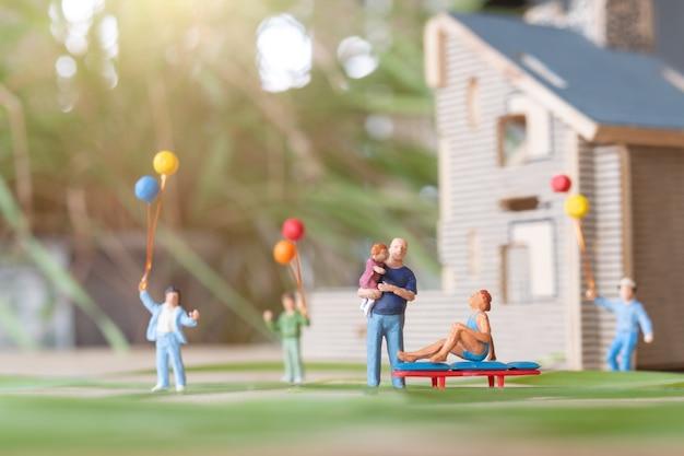 Miniaturfamilie, die im hinterhofrasen spielt