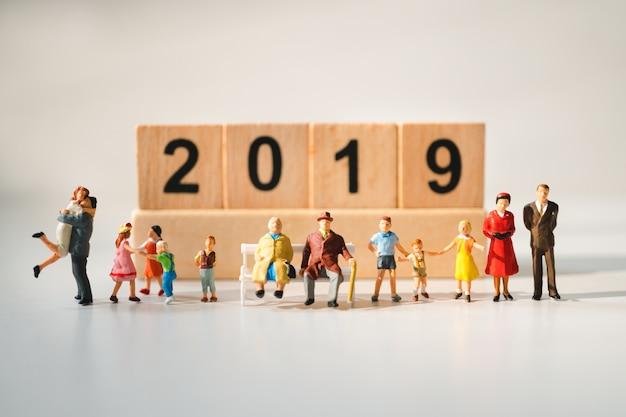 Miniaturfamilienleute, die mit hintergrund des holzblockjahres 2019 unter verwendung als familienkonzept stehen