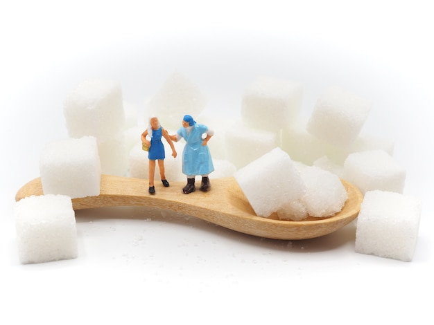 Miniaturfett und dünne frau mit zucker auf weißem hintergrund, gesundes lebensstilkonzept.
