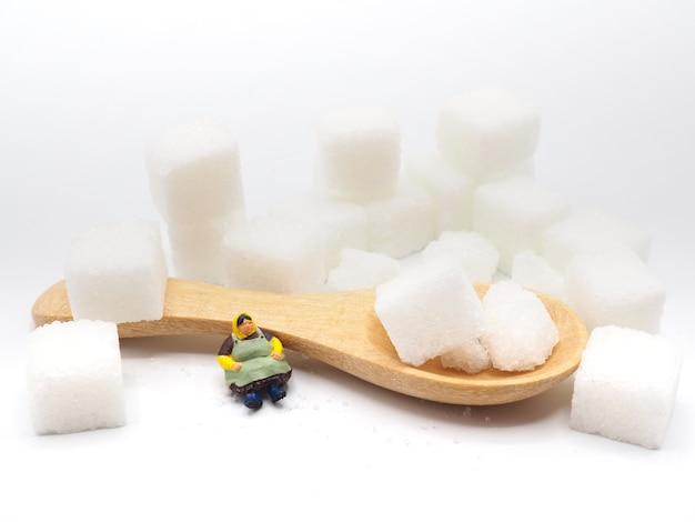Miniaturfettfrau mit zucker auf weißem hintergrund, gesundes lebensstilkonzept.