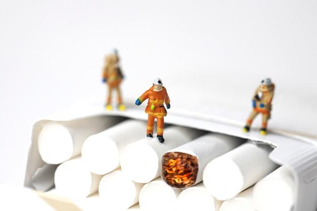 Miniaturfeuerwehrmänner und zigaretten auf weißem hintergrund