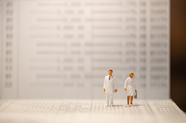 Miniaturfigur des doktors und der krankenschwester, die auf banksparbuch mit kopienraum steht.