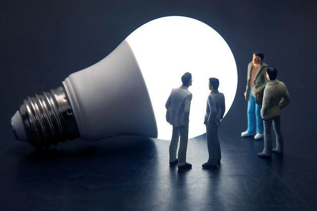 Miniaturfiguren menschen stehen in der nähe der mitgelieferten led-lampe