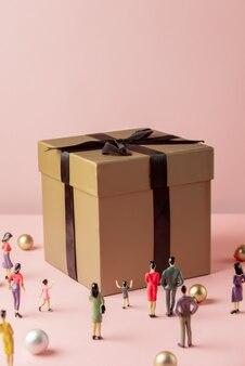 Miniaturfiguren von menschen und große geschenkbox